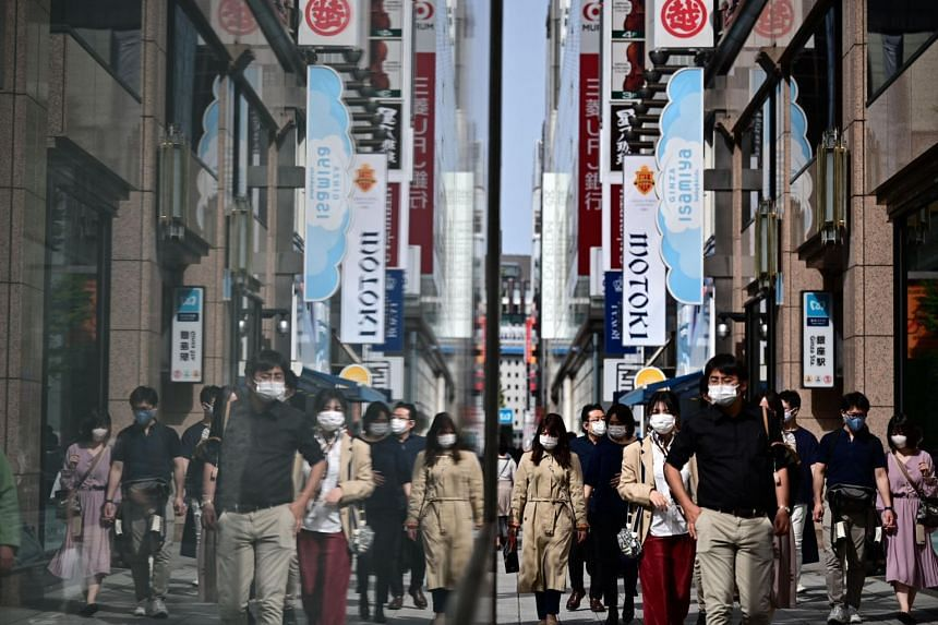 People walk along a street in the Ginza district in Tokyo on May 4, 2021.
