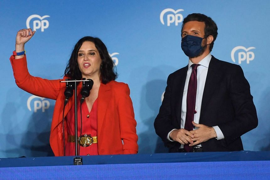 Ayuso (left) delivers a speech as she celebrates her victory beside PP leader Pablo Casado.