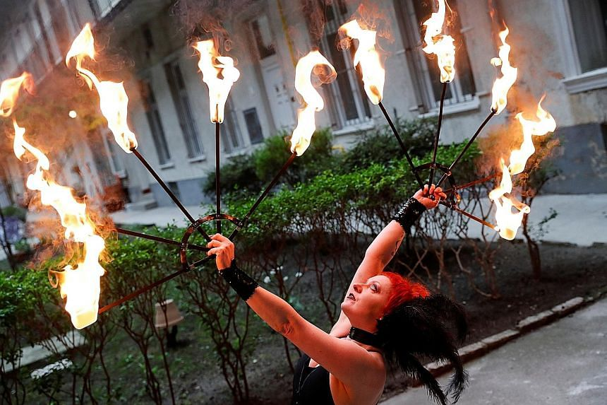 Hungarian circus artiste Eszter Kovacs, a member of the Taurin Circus Group, practising fire-juggling in the courtyard of her apartment block in Budapest, last week.