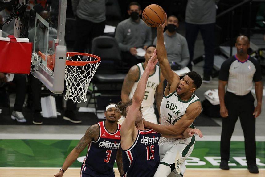 Milwaukee Bucks forward Giannis Antetokounmpo (right) shooting over Washington Wizards centre Robin Lopez (centre) during their NBA match on May 5, 2021.