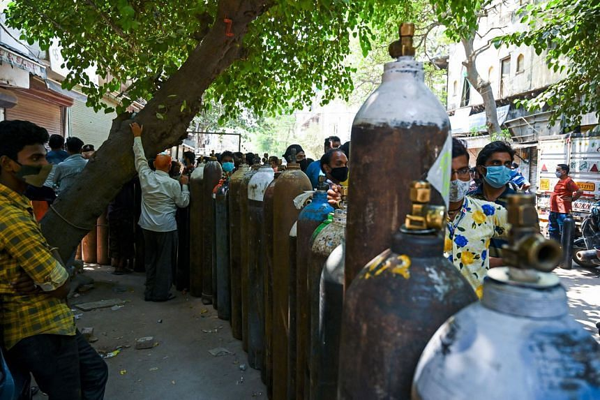 People waiting in line to fill oxygen cylinders for Covid-19 patients at a refilling centre in New Delhi on May 5, 2021.