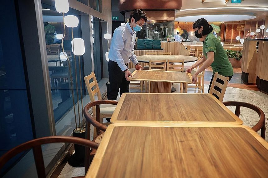 Restaurant manager Ken Lim and supervisor Annie Wong shifting tables to accommodate smaller dining group sizes at Yun Nans restaurant at Westgate mall on May 5.