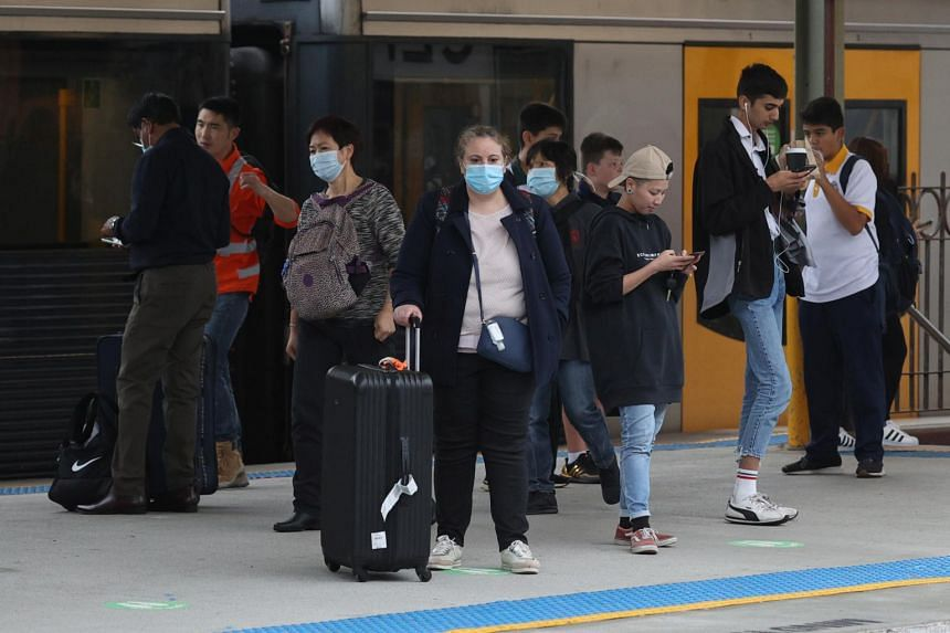 Commuters, some wearing masks, stand on a train platform at Central Station in Sydney on May 6, 2021.