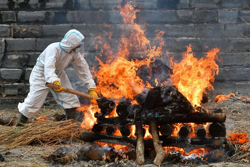 A man in PPE checking the funeral pyre of a Covid-19 victim at a cremation ground in Kathmandu, Nepal, on May 5, 2021.