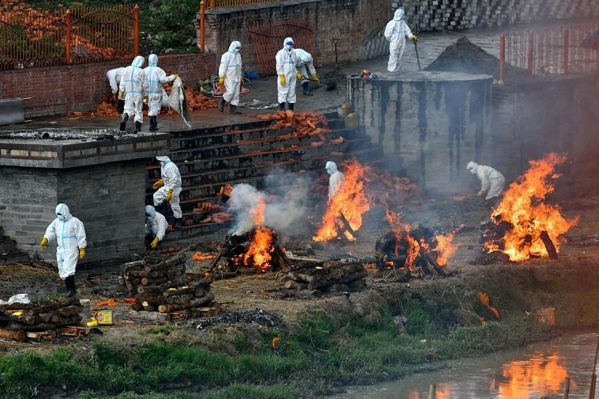 Workers wearing PPE working among the funeral pyres of people who died from Covid-19, in Kathmandu on May 5, 2021.