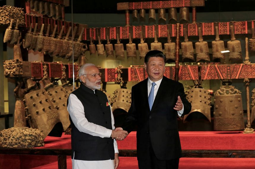 In a photo taken on April 27, 2018, Chinese President Xi Jinping and Indian Prime Minister Narendra Modi shake hands as they visit the Hubei Provincial Museum in Wuhan.