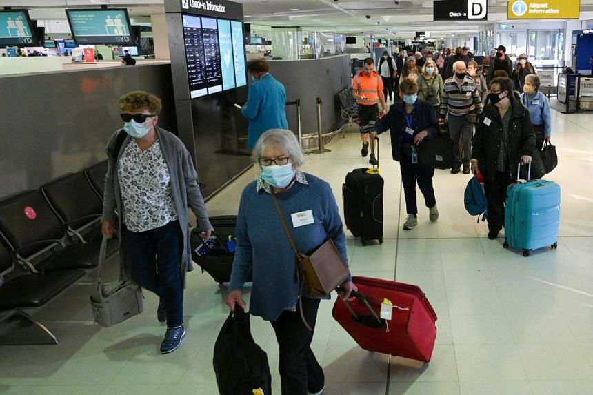 In a photo taken on April 19, 2021, travellers proceed to the check-in counters for New Zealand flights at Sydney International Airport.