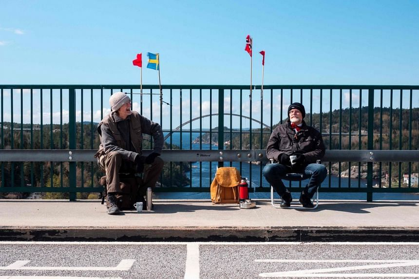 Pontus Berglund (left) sits on the Swedish side while his brother Ola sits on the Norwegian side of the old bridge of Svinesund on May 1, 2021.