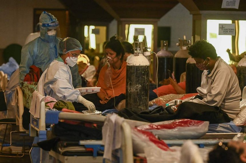 Healthcare workers attend to Covid-19 patients inside a banquet hall temporarily converted into a care centre in New Delhi, on May 7, 2021.