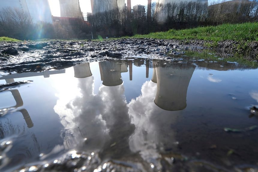 A power plant complex is reflected in a puddle in Neurath, Germany.