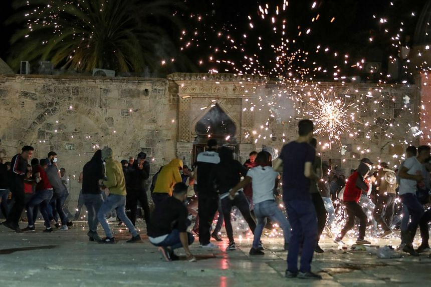 Palestinians react as Israeli police fire stun grenades during clashes at the compound that houses Al-Aqsa Mosque.