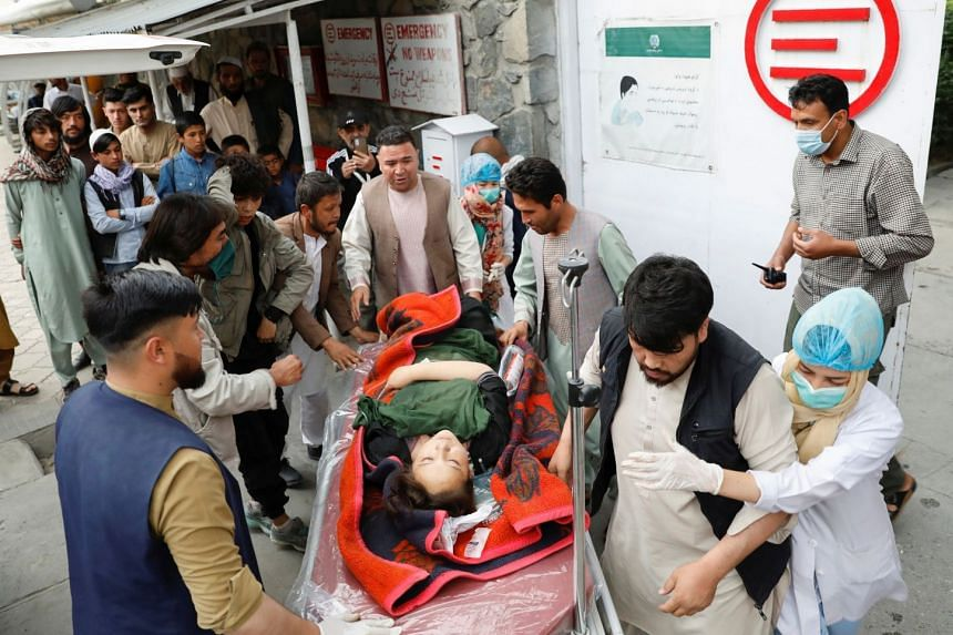 An injured woman is transported to a hospital after a blast in Kabul, on May 8, 2021.
