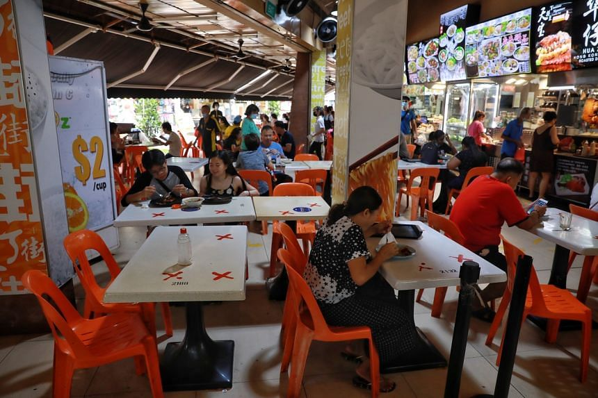 The lunch crowd at 201 Tampines Street 21 hawker centre on May 8, 2021. The reduced permissible group size of five people takes effect today.