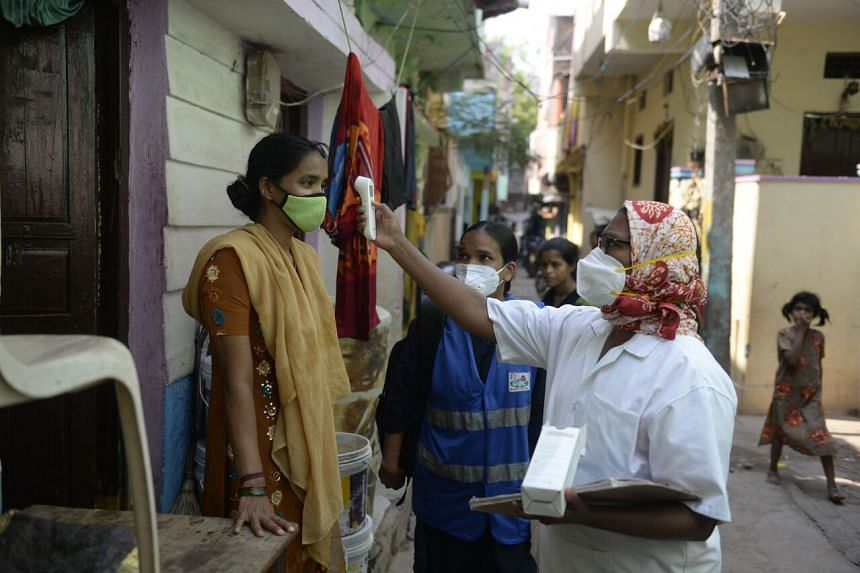 A health worker checks the temperature of a woman during a door-to-door survey to monitor for Covid-19 symptoms in residents of a low income neighbourhood in Hyderabad, on May 6, 2021.