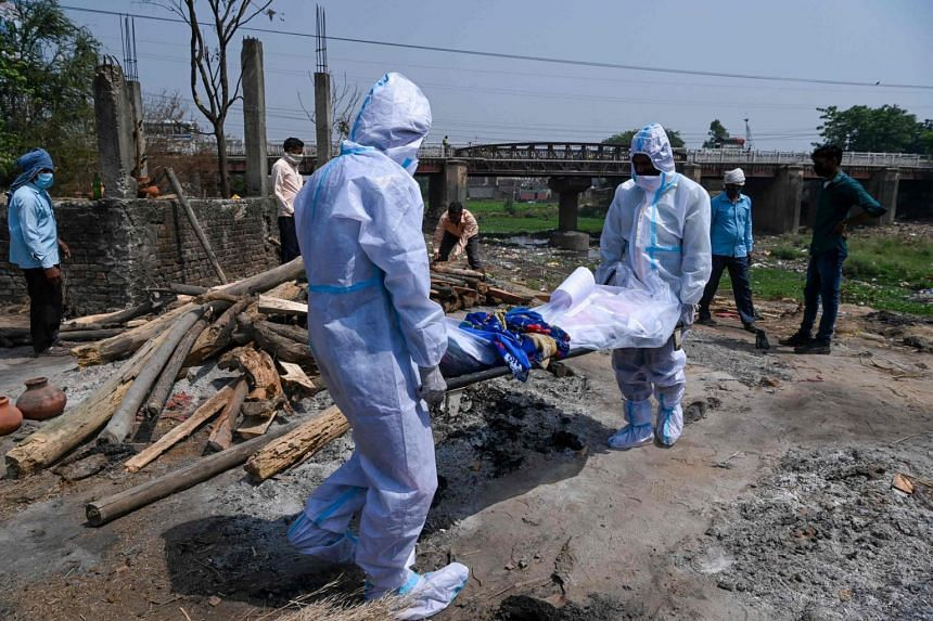 Relatives wearing personal protective equipment suits carry the dead body of a person who died due to the coronavirus at a crematorium in Moradabad.