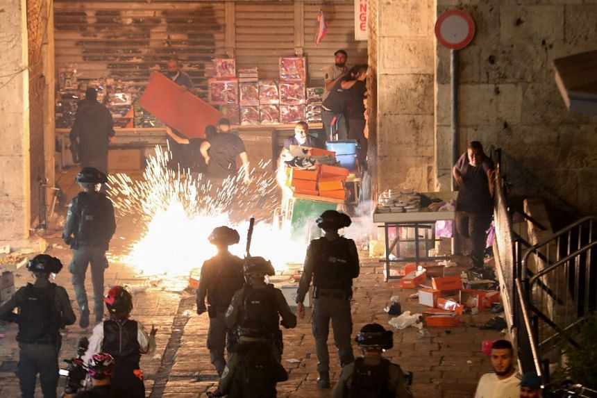 Palestinians react as Israeli police fire a stun grenade during clashes at Damascus Gate in Jerusalem's Old City, on May 9, 2021.