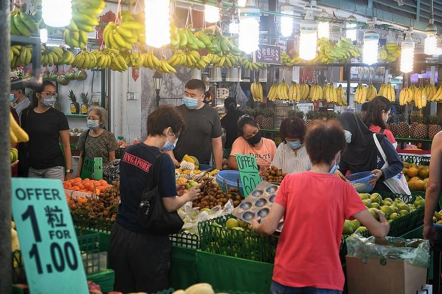 Shoppers at the Toa Payoh Lorong 7 market yesterday morning. The rule reducing group sizes to five people also applies to households. The breakfast crowd at the Kim Keat Palm Market and Food Centre in Toa Payoh Lorong 7 yesterday, with snaking queues