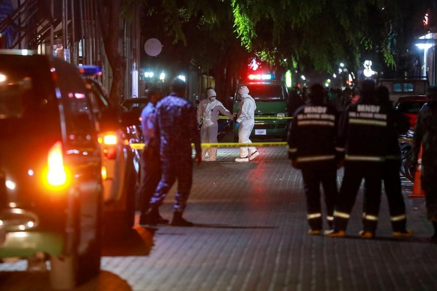 Police officers stand guard outside the cordoned-off area of a blast in Male, Maldives, on May 8, 2021.