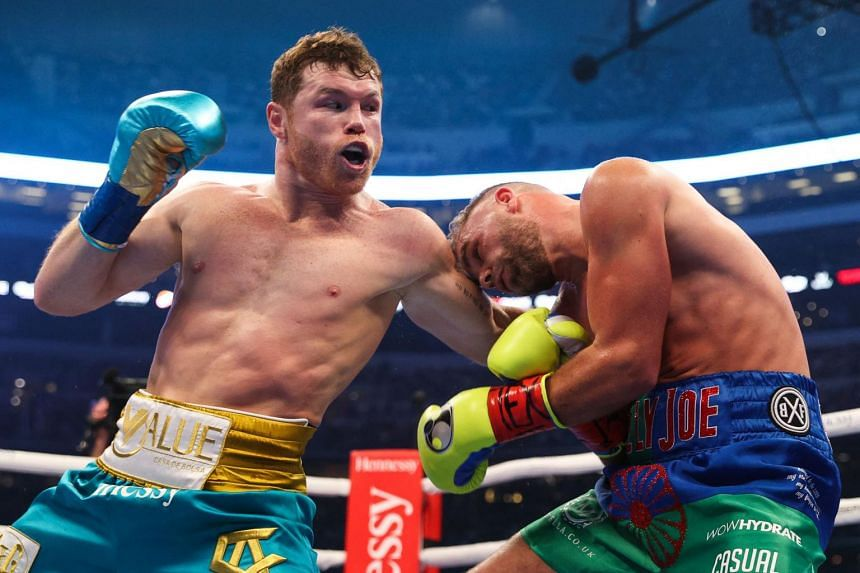 """Mexican boxer Saul """"Canelo"""" Alvarez (left) throughs a jab at British boxer Billy Joe Saunders during their super middleweight title fight at the AT&T Stadium in Texas, on May 8, 2021."""