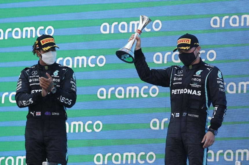 Mercedes' Lewis Hamilton (left) and Valtteri Bottas celebrate on the podium after the Spanish Grand Prix in Barcelona on May 9, 2021.