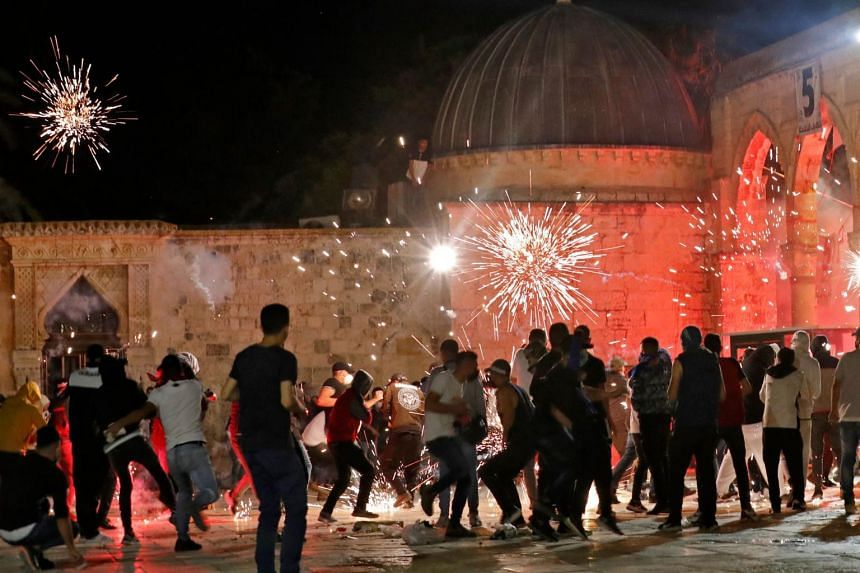 Stun grenades burst in the air amid clashes between Palestinian protesters and Israeli security forces at the al-Aqsa mosque compound in Jerusalem, on May 7, 2021.