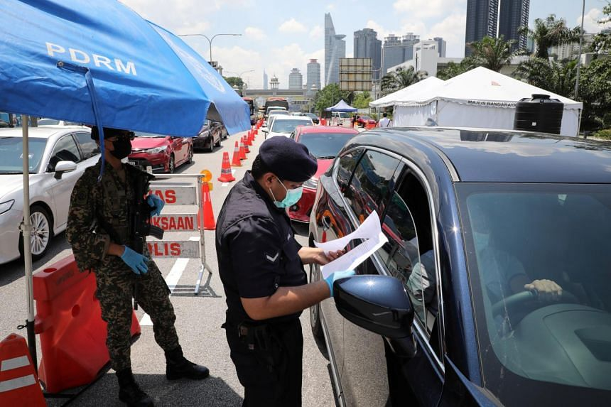 A police officer checks the documents of a driver in Petaling Jaya, Malaysia, on May 10, 2021.