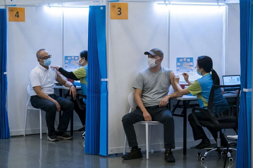 People receive a dose of China's Sinovac vaccine at a community vaccination centre in Hong Kong on February 23, 2021.