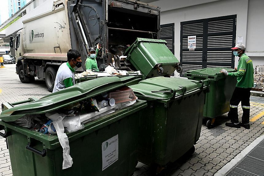 Workers carrying out manual waste collection at Alkaff CourtView in Bidadari estate on May 8, 2021.