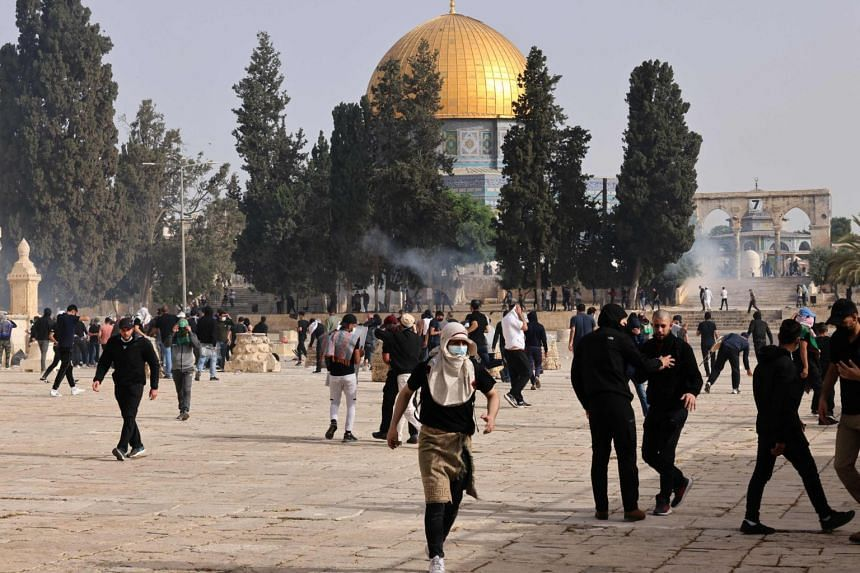 Palestinians run for cover from tear gas fired by Israeli security forces at Jerusalem's Al-Aqsa mosque compound on May 10, 2021.