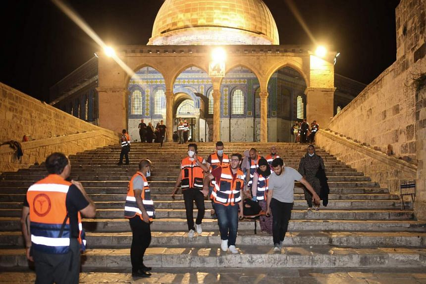 A wounded person evacuated during clashes between Israeli security forces and Palestinian protestors in Jerusalem's al-Aqsa mosque compound on May 10, 2021.