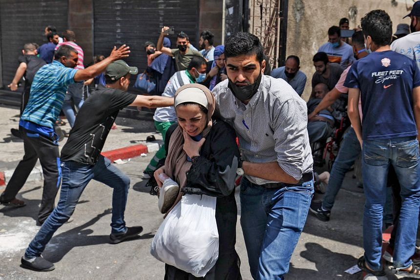 Palestinians evacuating a building targeted by Israeli bombardment in Gaza City on May 11, 2021.