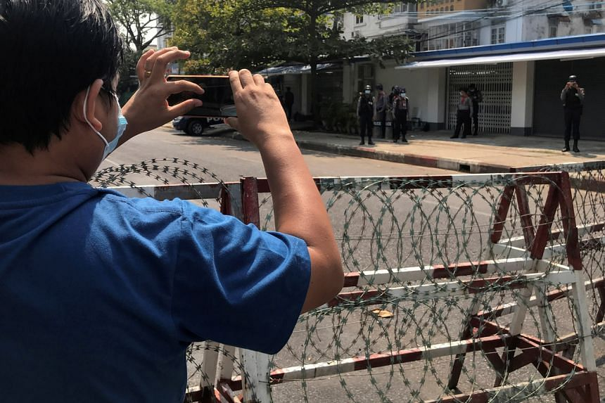 A journalist and a police officer take pictures of each other as people protest in Yangon, on Feb 23, 2021.
