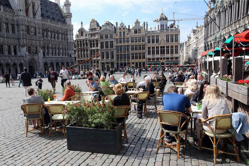 People sit at outdoor terraces at the Grand Place in Brussels, on May 9, 2021.