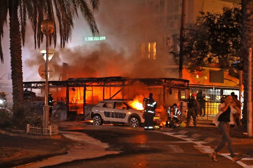 Firefighters extinguish a burning car in the town of Holon near Tel Aviv, after rockets were launched towards Israel from the Gaza Strip, on May 11, 2021.