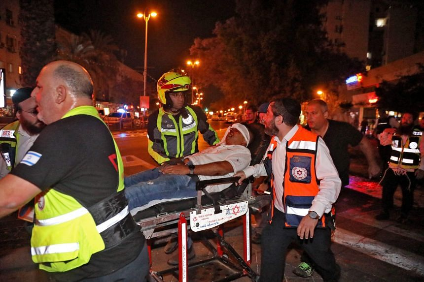 Israeli emergency services transport an injured man in the town of Holon near Tel Aviv, on May 11, 2021.