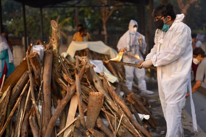 A family member performs the final rites for a Covid-19 victim at a cremation ground in New Delhi on May 10, 2021.