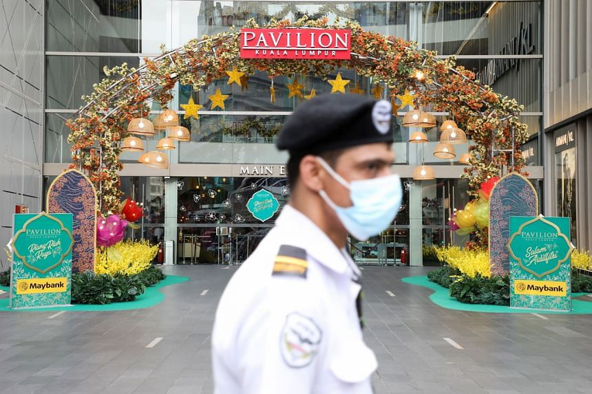 A security guard is seen outside a closed mall during a lockdown in Kuala Lumpur on May 11, 2021.