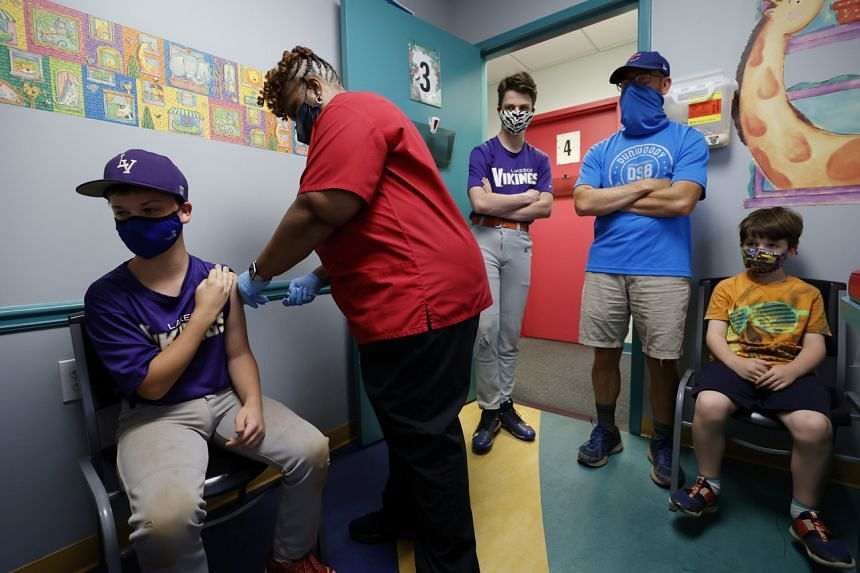 Family members look on as 12-year-old Jack Frilingos is inoculated with Pfizer's vaccine at a pediatric centre in Decatur, Georgia, on May 11, 2021.