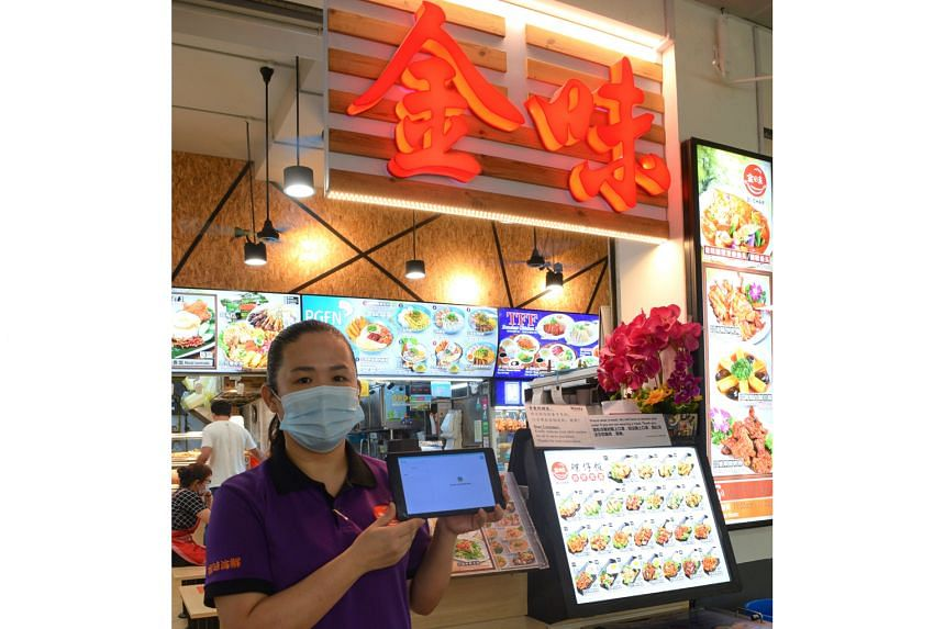 A Kimly Seafood worker (above) holding a digital menu at its zichar outlet in Bukit Batok.