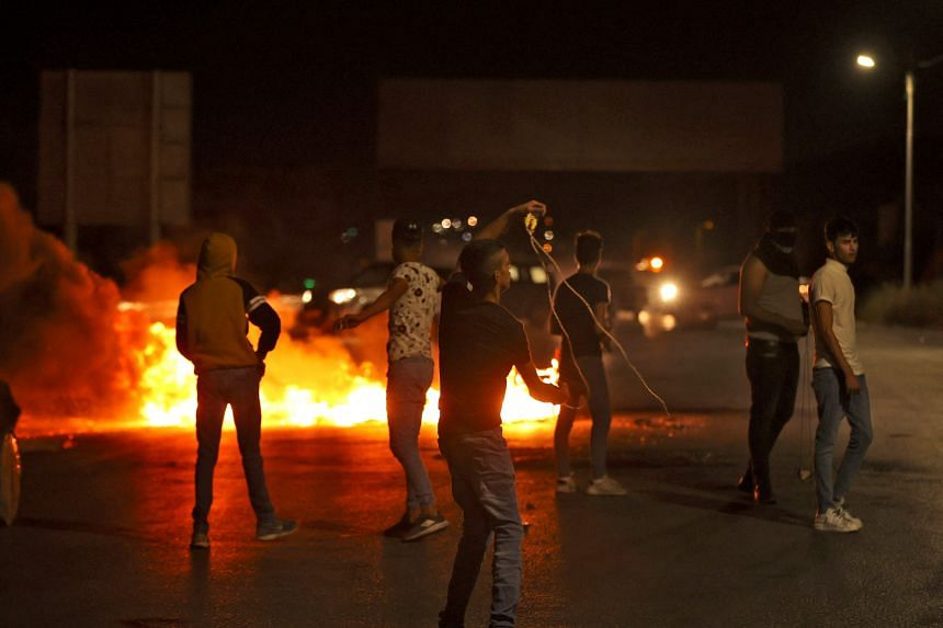 Palestinians hurling stones during clashes with Israeli security forces at Hawara checkpoint, south of Nablus, on May 11, 2021.