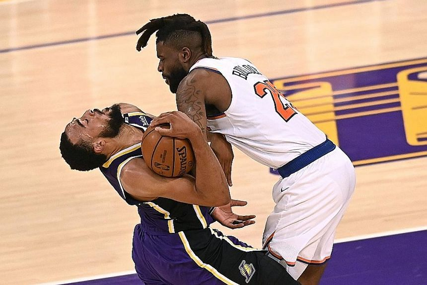 Los Angeles Lakers' Talen Horton-Tucker is fouled by Reggie Bullock of the New York Knicks during their 101-99 overtime win.