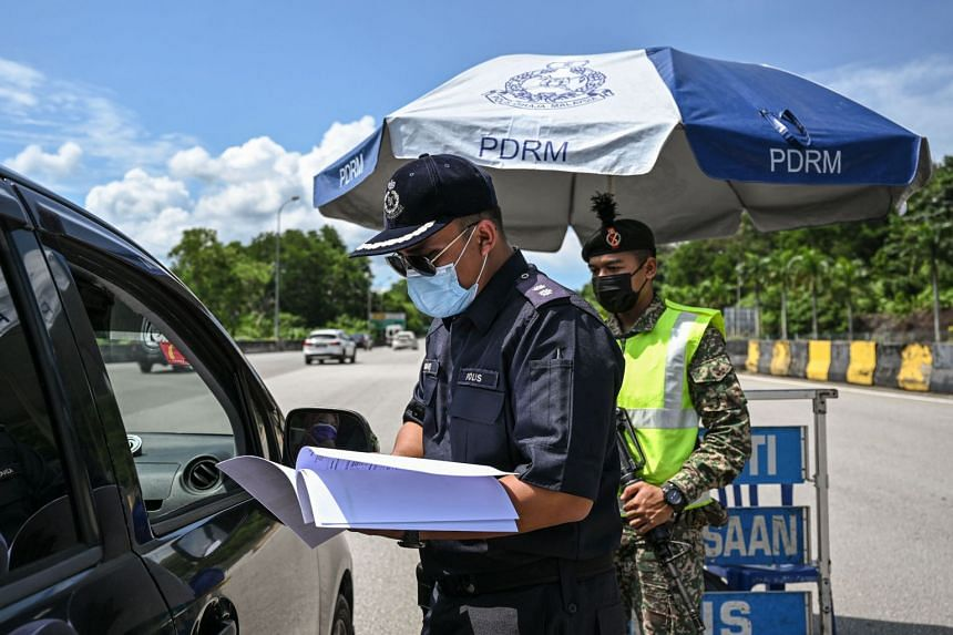 A policeman checks documents at a roadblock on the East Coast Expressway (Kuala Lumpur–Karak) during a partial lockdown in Bentong, on May 11, 2021.
