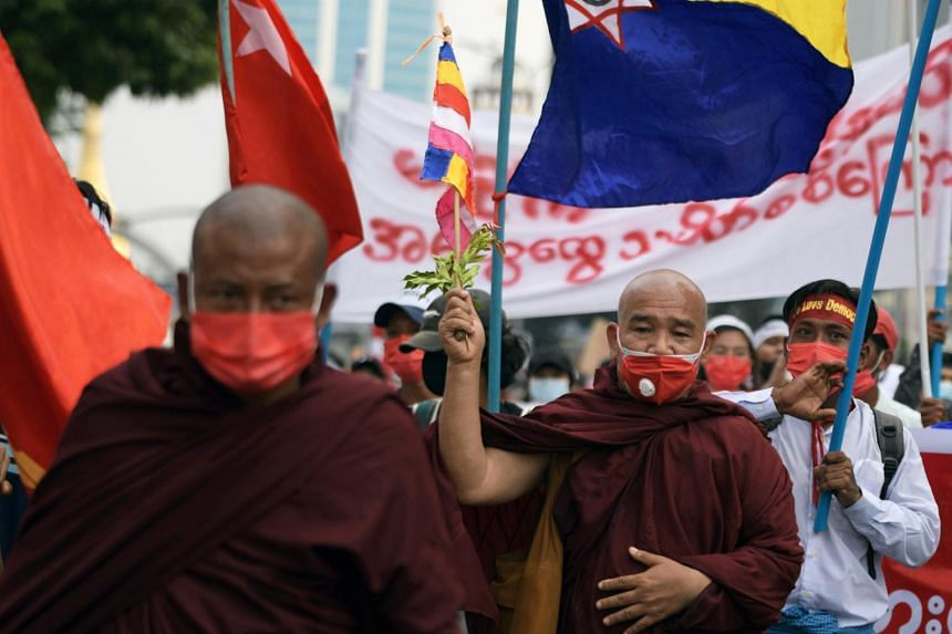 A Buddhist monk holds a flag during a protest against the military coup in Yangon, on Feb 22, 2021.