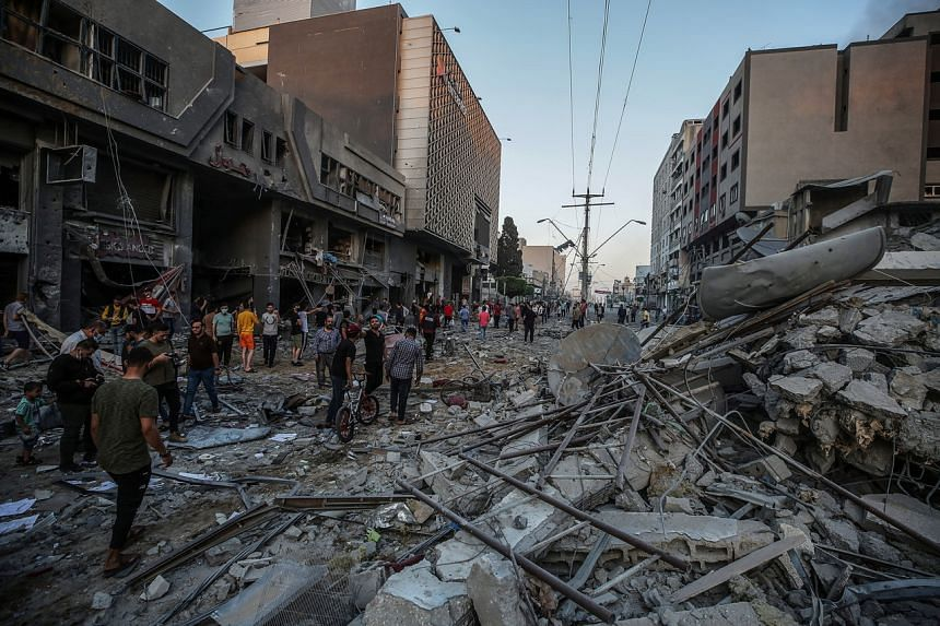 Palestinians are seen inspecting debris left behind after an Israeli strike in Gaza City on May 12, 2021.