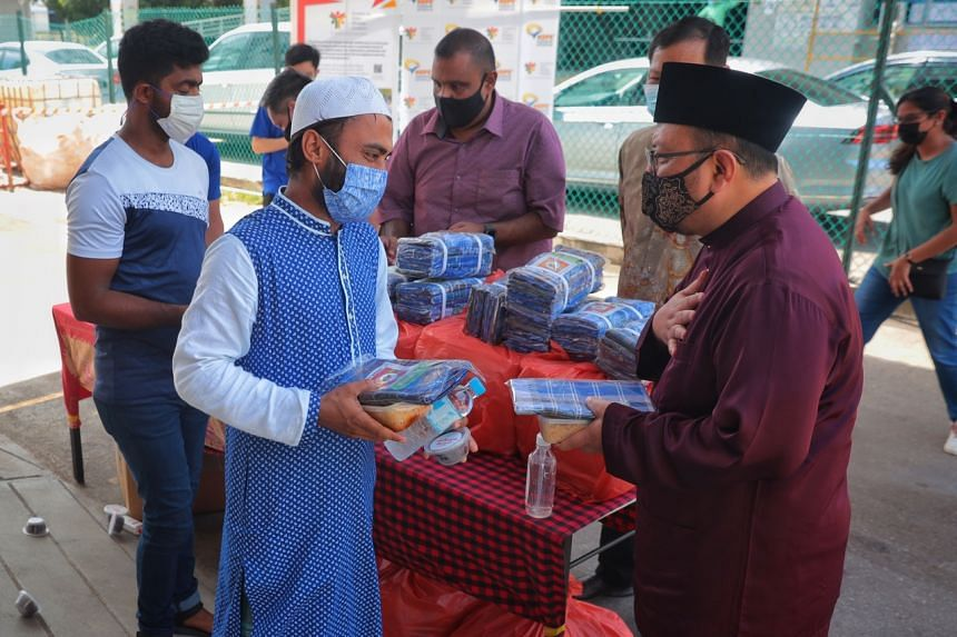 A migrant worker receives food and lungi from Deputy Mufti Ustaz Mohammad Hannan Hassan (right) at a dormitory in Tuas View Square.