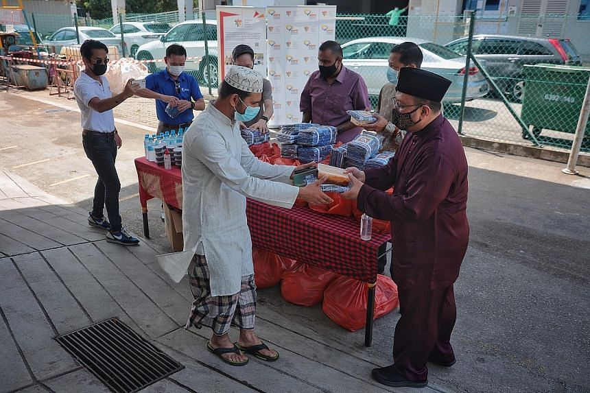 A resident of a dormitory at Tuas View Square receiving a festive meal and a sarong from Deputy Mufti Mohammad Hannan Hassan yesterday. With them are (from right) Mr Tung Yui Fai, chief of the Ministry of Manpower's Assurance, Care and Engagement (Ac