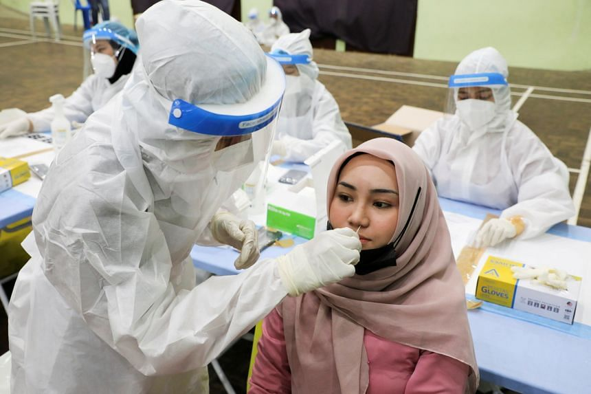 A medical worker collecting swab samples from a woman for a Covid-19 test, in KL on May 11, 2021.