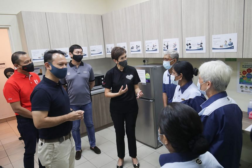 Manpower Minister Josephine Teo (centre) and Senior Minister of State Zaqy Mohamad (second from left) speaking to cleaners on May 14, 2021.