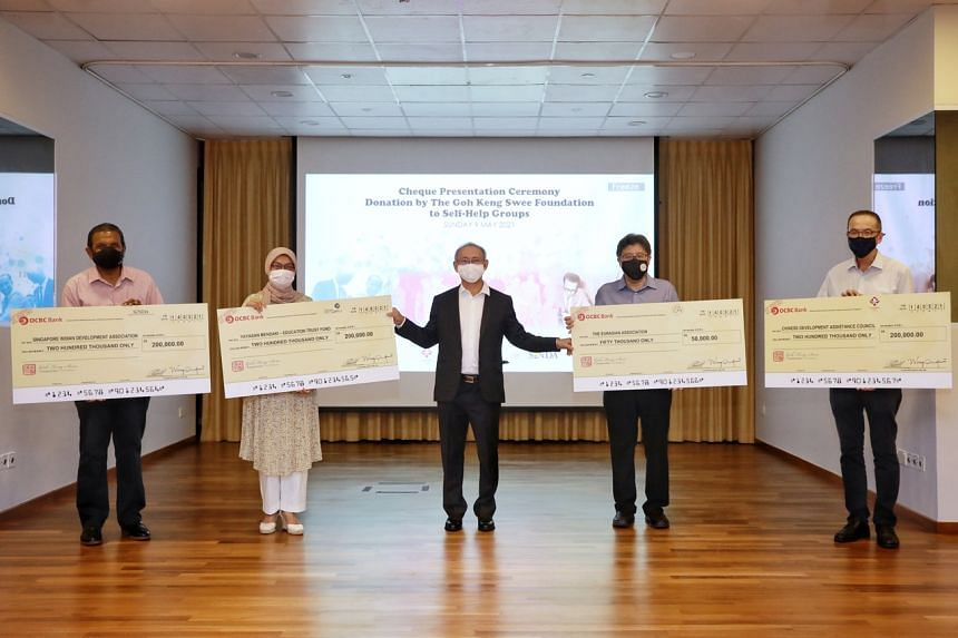 Director of the Goh Keng Swee Foundation Wong Kok Hoi (middle) presenting the cheques to key representatives of the four communities in Singapore.