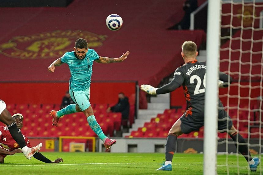 Liverpool's Roberto Firmino heads past Manchester United goalkeeper Dean Henderson for their second goal, on May 13, 2021.